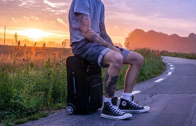 chico en pantalon corto sentado en una maleta